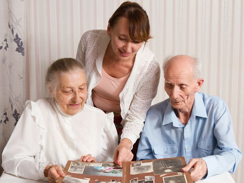 caregiver looks at photo book with an elderly couple