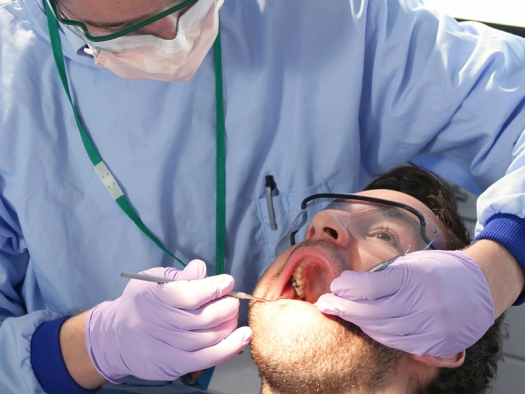 dentist working on man with mouth open