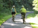 two women bicycling along paved, wood-lined path