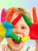 Child laughing with multi-colored paint on his hands