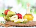 Apple cider vinegar in glass bottle and ripe fresh apples on wooden table